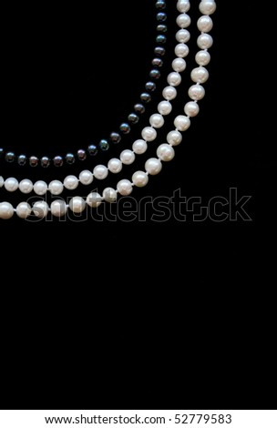 White and black pearls on the black silk as background - stock photo