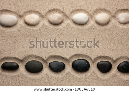 White and black stones lying  in  the sand, with space for your text  - stock photo