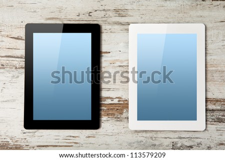 white and black tablet touch computer gadget with blue screen on a background of wood. - stock photo