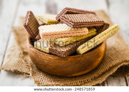 White and black wafer biscuits in wooden bowl on linen - stock photo