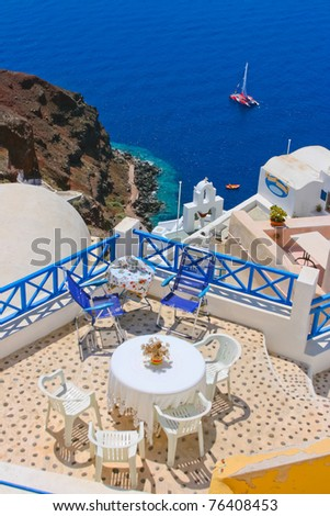 White and blue chairs and a small table on beautiful terrace in Santorini with Caldera view and Aegean sea. As always clear blue sky in hot Greece. Great atmosphere for vacation and holidays. - stock photo