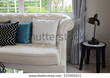 white and blue pillows on a white leather couch in vintage living room - stock photo