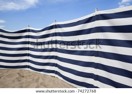 white and blue striped windbreak at the beach - stock photo