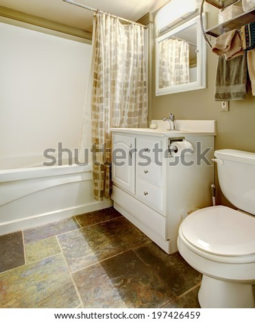 White and brown bathroom with tile floor and white tub, toilet and antique bathroom vanity - stock photo