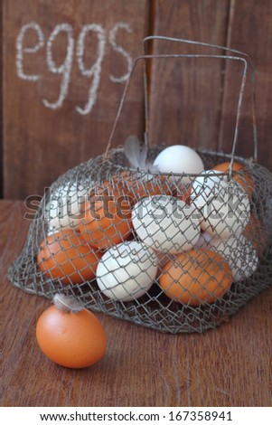 white and brown chicken eggs in a basket on a brown table