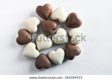 White and brown chocolates in the shape of a heart - stock photo