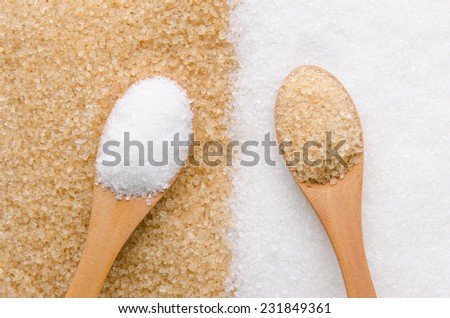 White and brown sugar in wood spoon.