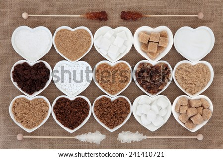 White and brown sugar selection in heart shaped bowls with crystal lollipop sticks over hessian background. - stock photo