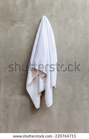 White and clean towel is hanging on the exposed concrete wall in the bathroom.
