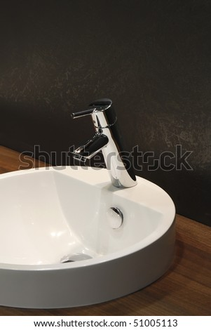 White and clean washbasin and chrome tap - stock photo