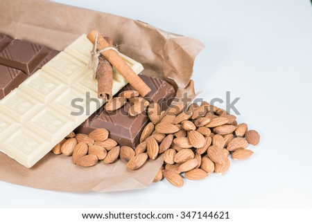 white and dark chocolate, almonds, cinnamon, cocoa. shallow DOF; color toned image - stock photo