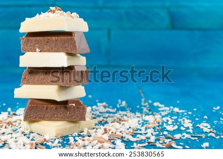 White and dark roughly cut chunks of a chocolate on vintage blue background - stock photo