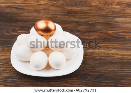 White and gold chicken eggs on the plate, wooden background - stock photo