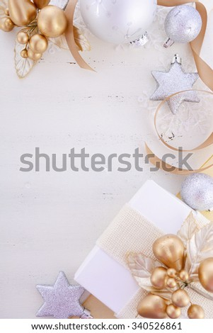 White and gold theme festive Christmas background with decorated borders including gifts and decorations on a rustic white wood table.