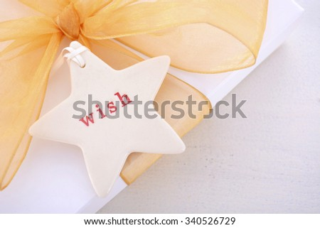 White and gold theme festive Christmas background with decorated borders on a rustic white wood table, closeup on gift and wish tag.   - stock photo