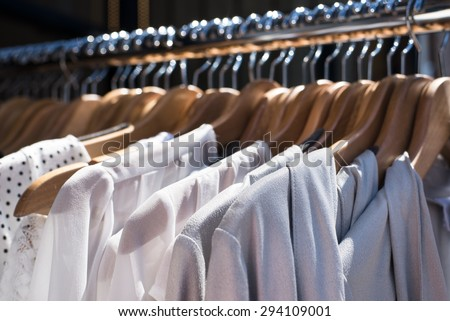 white and gray tone clothes hanging on a rack in a designer clothes store, selective focus, horizontal - stock photo