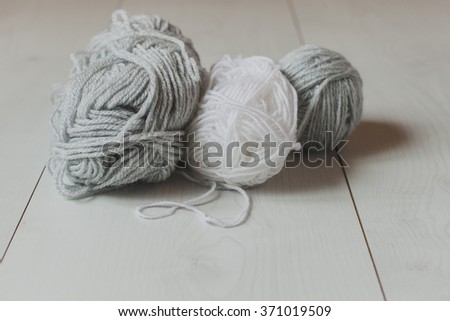 White and gray yarn on a white table.  - stock photo