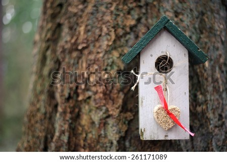 White and green birdhouse with hanging heart made from seeds - stock photo