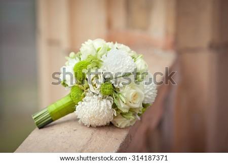 White and green bouquet on a stone parapet with rose, eustoma, chrysanthemum and dahlia. Horizontal closeup image - stock photo
