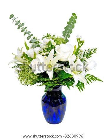 White and green flower arrangement centerpiece in blue vase with lilies isolated on white - stock photo