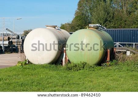 white and green storage tanks - stock photo