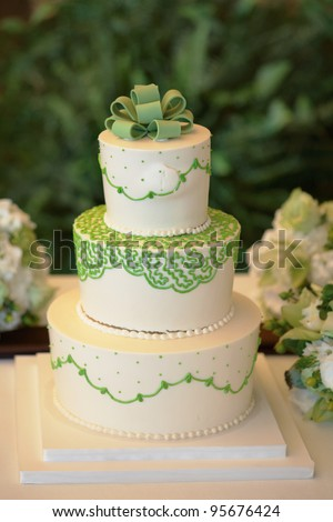 White and green wedding cake with flowers at reception - stock photo