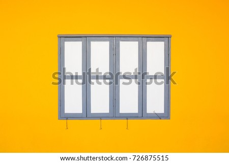 white and grey wooden windows on yellow wall background