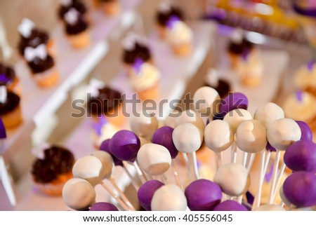 White and mauve lollipops with many cake in background - stock photo