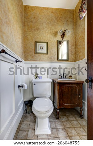 White and mocha bathroom interior with tile floor and antique vanity cabinet - stock photo