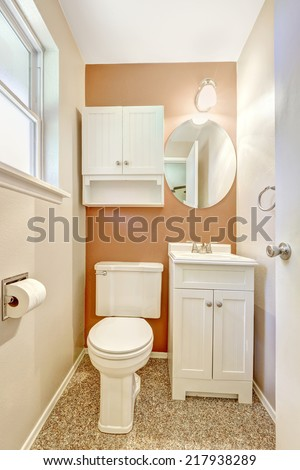 White and orange small bathroom with white cabinet and mirror