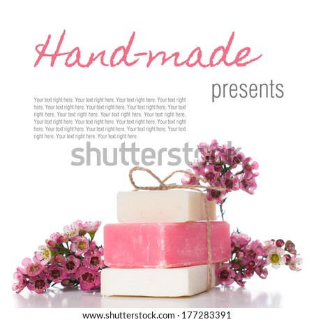 White and pink handmade soap and pink cherry blossoms on a white background, isolated. Gifts and handmade souvenirs. - stock photo