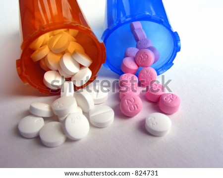 White and pink pills with pill vials on white background