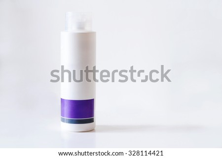 White and purple plastic bottle isolated on white background with beauty cream for skin care - stock photo