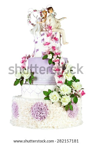 White and purple wedding cake decorated with white roses and purple orchids with a couple a bride and groom on top. Isolated on white background - stock photo