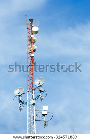 White and red color antenna repeater tower on blue sky, telecommunication concept - stock photo