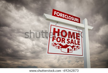 White and Red Foreclosure Home For Sale Real Estate Sign Over Ominous Cloudy Sky. - stock photo