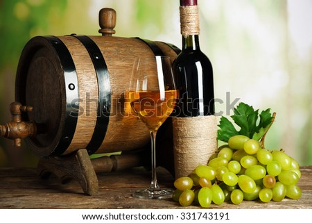 White and red grape with wine bottle near barrel on wooden table, close up