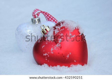 White and red heart shaped ornaments in fresh fallen snow