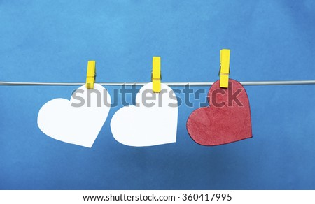 white and Red hearts with clothespins hanging on clothesline  on blue background. date, love Valentines Day concept - stock photo