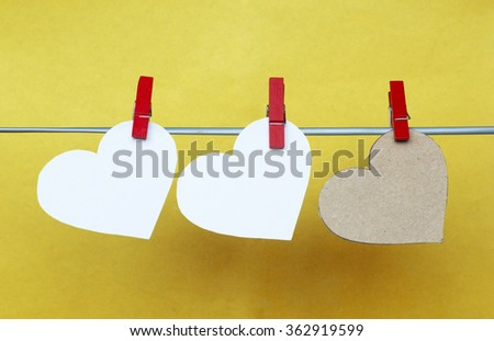 white and Red hearts with clothespins hanging on clothesline on yellow background. Romantic date, love Valentines Day concept - stock photo