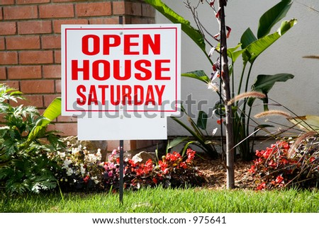 White and red open house sign in front of the small suburban house. - stock photo