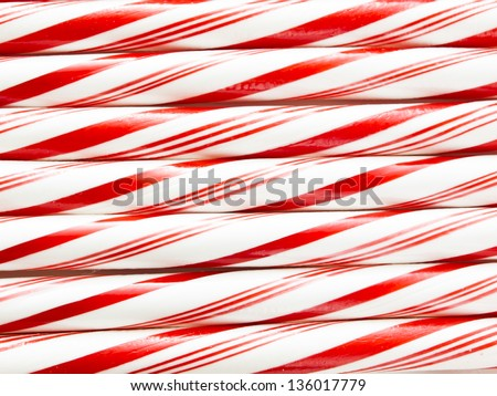White and red peppermint candy canes in a row on white background. - stock photo