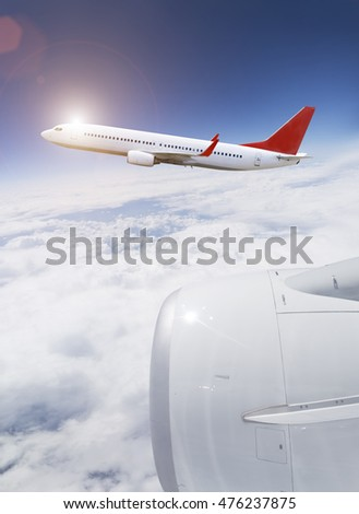 White and red plane flying over the cloud in blue sky