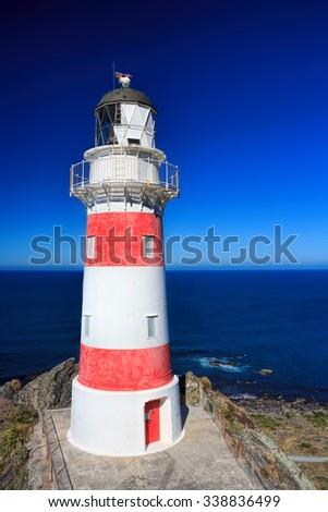 White and red striped lighthouse, location - Cape Palliser bay lighthouse, Wairarapa, North Island, New Zealand - stock photo
