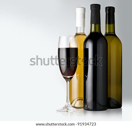 White and red wine bottles with one glasses on the white background - stock photo