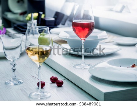 White and red wine in a glass. Light background