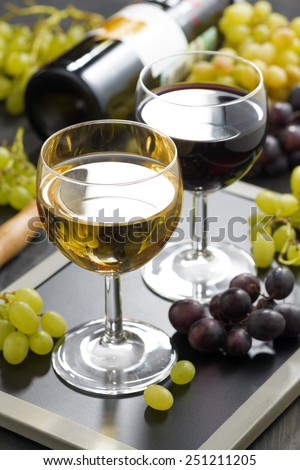 white and red wine in glasses, grapes in the background, vertical, close-up - stock photo