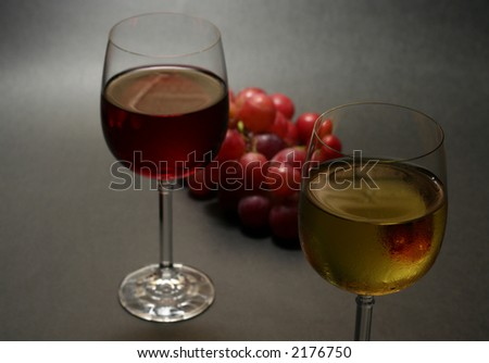 white and red wine with grapes on dark background, narrow focus