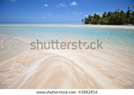 White and rose sand beach front of blue lagoon and tropical island - stock photo