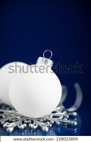 White and silver christmas ornaments on dark blue background with space for text. Merry christmas card. Winter holidays. Xmas theme. - stock photo